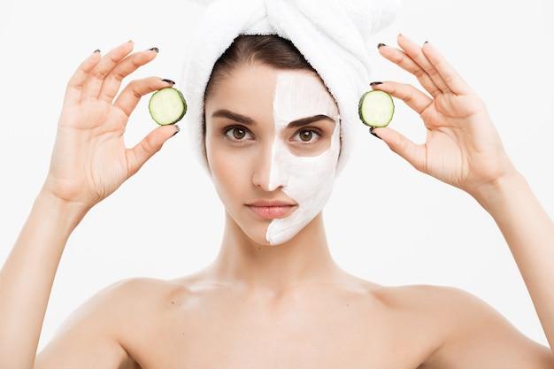 Conceito de cuidados com a pele beleza juventude - retrato mulher caucasiana bonita aplicar creme e segurando pepino fresco na frente de seu rosto. isolado sobre a parede branca.