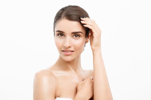Conceito de cuidados com a pele beleza linda mulher caucasiana rosto retrato bela beleza jovem modelo feminino garota tocando seu rosto pele bochechas mãos dedos moda beleza modelo isolado no branco