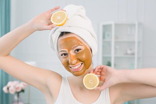 Conceito de cuidados com a pele beleza. mulher caucasiana atraente toalha branca com máscara facial marrom no rosto detém frutas cítricas na mão no espaço claro. procedimentos de spa e máscara de creme na pele