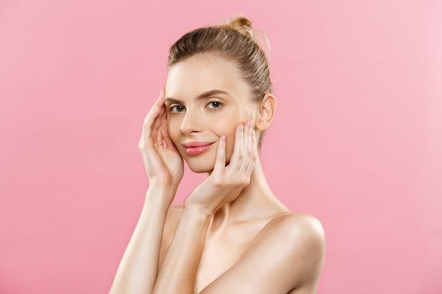 Conceito de cuidados com a pele - charming young caucasian woman with perfect makeup photo composition of brunette girl. isolado no fundo cor-de-rosa com espaço de cópia.