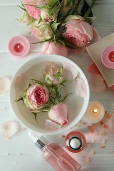 Conceito de cuidados com a pele com óleo essencial de rosa na mesa de madeira branca