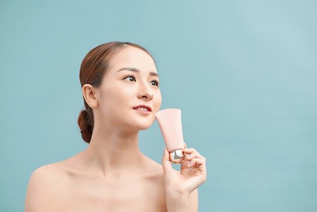Conceito de cuidados com a pele da juventude da beleza - retrato de rosto de mulher branca bonita segurando e apresentando um tubo de creme