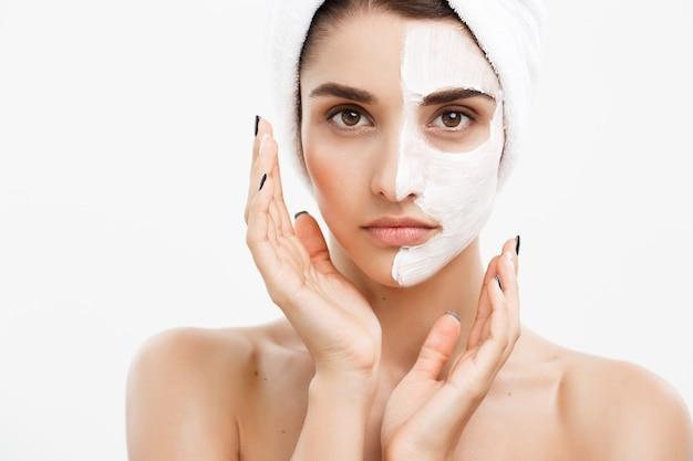 Conceito de cuidados com a pele de beleza - retrato de rosto de mulher branca bonita aplicando máscara de creme na parede branca de sua pele facial.