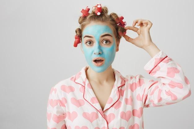 Conceito de cuidados com a pele e beleza. linda mulher em pijamas e modeladores de cabelo para tirar máscara facial
