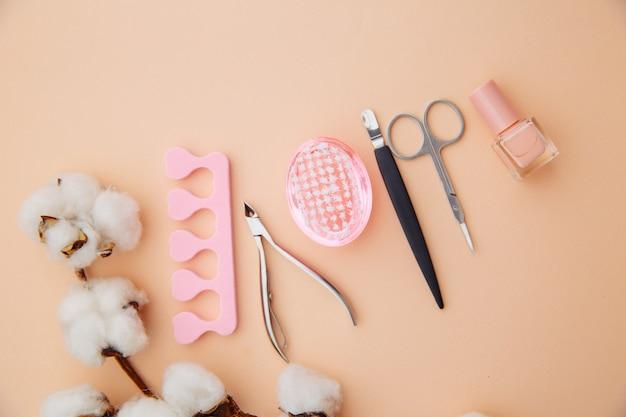 Conceito de cuidados de beleza. um conjunto de ferramentas profissionais para manicure e pedicure na superfície rosa