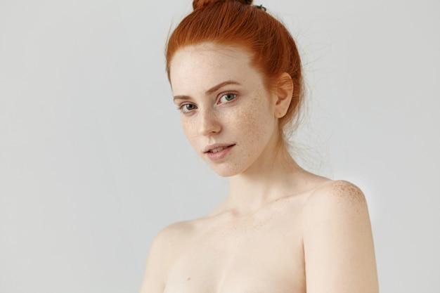 Conceito de cuidados de pessoas, juventude, beleza e pele. retrato de mulher ruiva jovem bonita posando de topless olhando com sorriso misterioso sutil, tendo sardas em todo o rosto e ombros