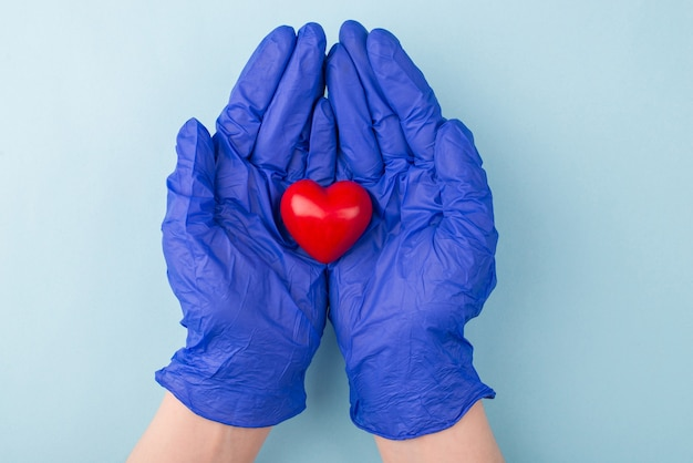 Conceito de cuidados de saúde. acima em cima, feche a foto de mãos segurando um pequeno coração vermelho isolado sobre a superfície azul