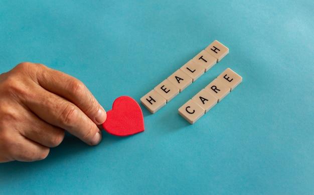 Conceito de cuidados de saúde com a mão, colocando um coração com telhas de carta. copie o espaço. foco seletivo.