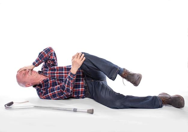 Conceito de cuidados de saúde, dor, estresse e idade. homem idoso com dor no joelho, sobre fundo branco