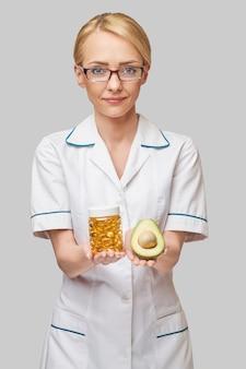 Conceito de cuidados de saúde e dieta - médico nutricionista ou cardiologista segurando óleo de peixe em cápsulas de vitamina d e ácidos graxos ômega-3 e abacate