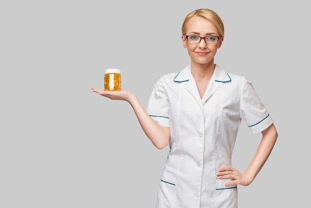 Conceito de cuidados de saúde e dieta - médico nutricionista ou cardiologista segurando óleo de peixe em cápsulas de vitamina d e ácidos graxos ômega-3