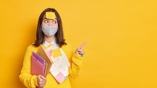 Conceito de cuidados de saúde e educação. aluna adolescente satisfeita usando máscara protetora contra pontos de coronavírus em uma parede amarela em branco demonstra os resultados de seu projeto cercada de papéis adesivos adesivos