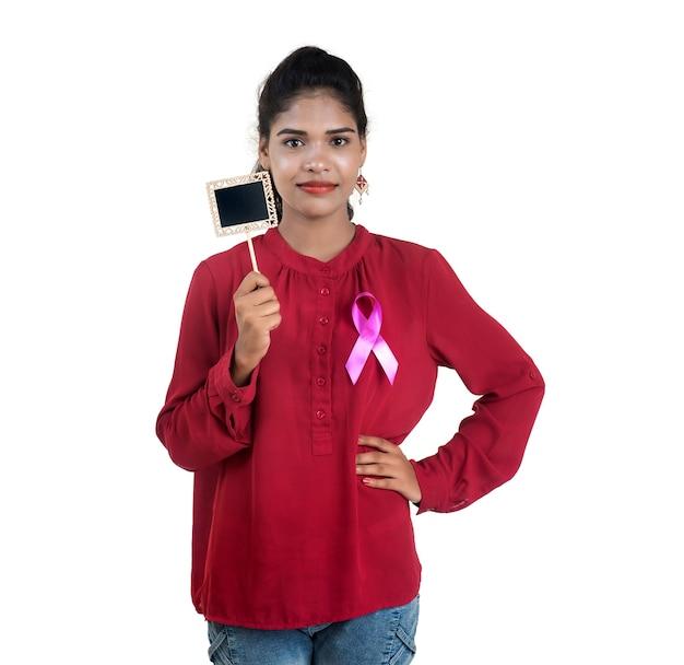 Conceito de cuidados de saúde e medicina - jovem com as mãos segurando uma fita rosa de conscientização do câncer de mama e uma pequena placa preta