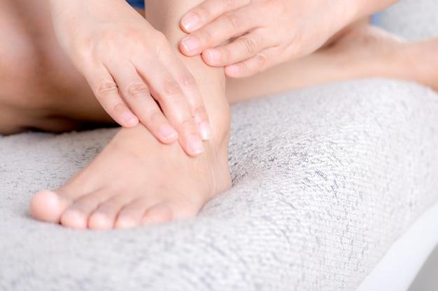 Conceito de cuidados de saúde e médico. closeup jovem mulher sentada no sofá e sentir dor no tornozelo e ela massageia o tornozelo em casa.