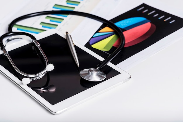 Conceito de cuidados de saúde e negócios. estetoscópio na tabuleta com papel de carta do relatório.