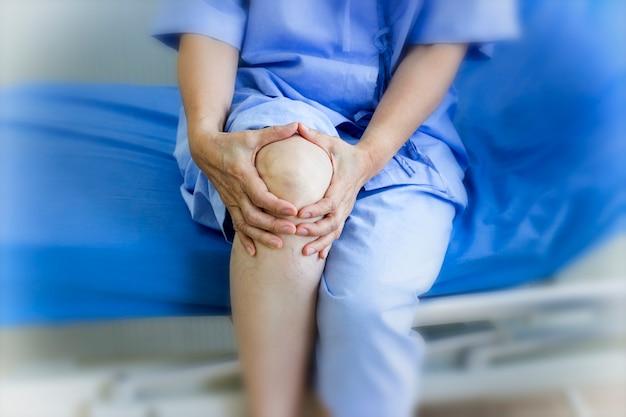 Conceito de cuidados de saúde; paciente idoso que sofre da dor do joelho no hospital.