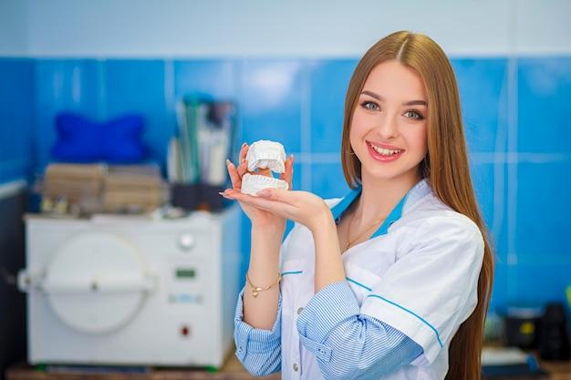 Conceito de cuidados de saúde. próteses dentárias. menina bonita em um jaleco branco segurando modelos de gesso dentais.