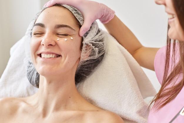Conceito de cuidados de spa, beleza, pele e corpo. jovem, cliente da clínica de cosmetologia, recebendo tratamento de beleza facial no salão spa. cosmetologista aplica creme hidratante no rosto da mulher sorridente.