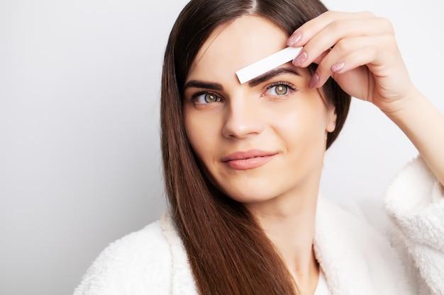 Conceito de cuidados, mulher segurando a faixa com cera para remover pêlos faciais