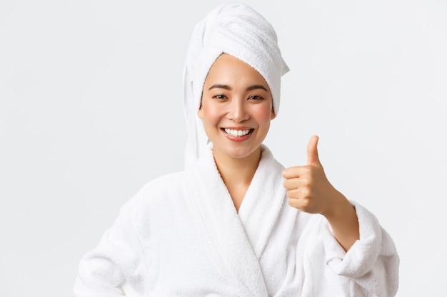 Conceito de cuidados pessoais, beleza das mulheres, banho e chuveiro. menina asiática feliz satisfeita em roupão de banho e toalha mostrando o polegar em aprovação, recomendar salão de spa ou produto de higiene, sorrindo satisfeito