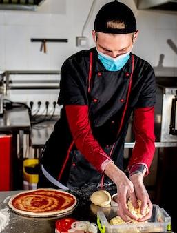 Conceito de culinária de pizza, chef com máscara médica colocando pasta de tamat na pizza