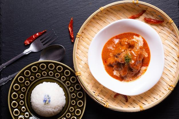 Conceito de culinária tailandesa caseiro curry vitela panang e thai reice em bachgroung preto com espaço de cópia