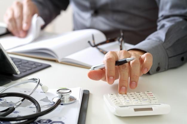 Conceito de custos e taxas de cuidados de saúde. a mão do doutor esperto usou uma calculadora para custos médicos no hospital.