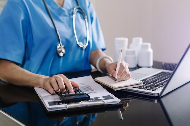Conceito de custos e taxas de saúde. a mão do médico inteligente usou uma calculadora e um smartphone, tablet para despesas médicas no hospital na luz da manhã