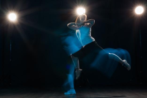 Conceito de dança, esporte, beleza e pessoas - jovem mulher dançando na escuridão saltou em luz colorida.