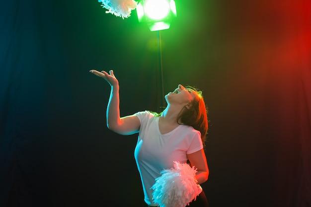Conceito de dança, esporte e pessoas - bela jovem dançando na escuridão com pompons e sorrindo.