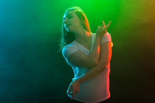 Conceito de dança, esporte e pessoas - garota líder de torcida dançando em plano de fundo multicolorido.