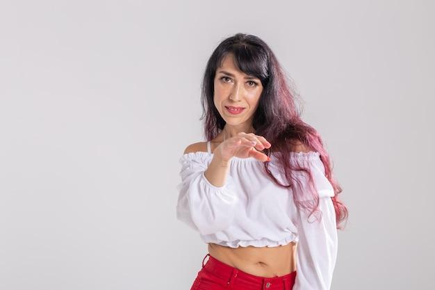 Conceito de dança latina, strip dance, contemporâneo e bachata lady - mulher dançando improvisação e movendo seus longos cabelos em um fundo branco com copyspace