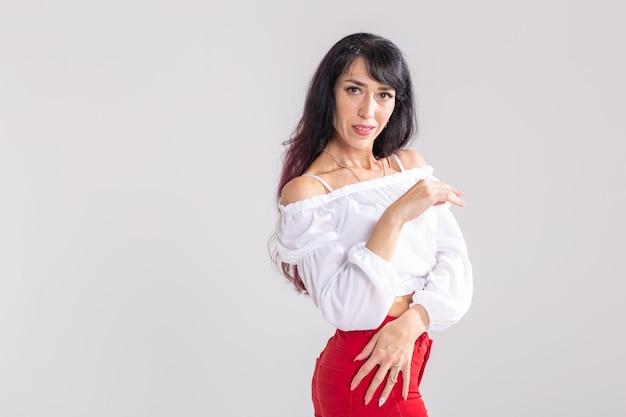 Conceito de dança latina, strip dance, contemporâneo e bachata lady - mulher dançando improvisação e movendo seus longos cabelos em um fundo branco com espaço de cópia