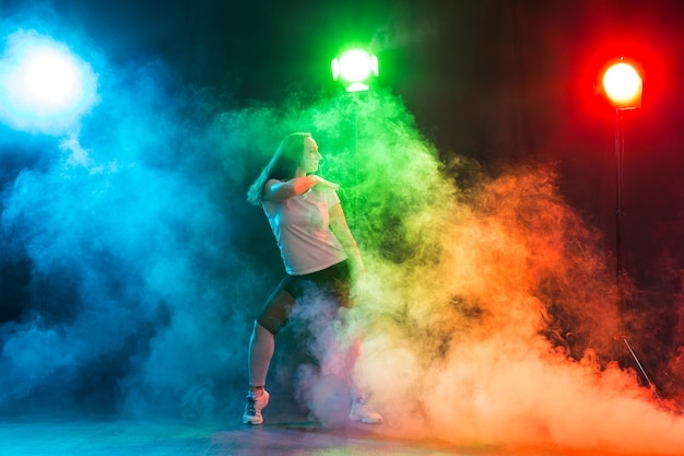 Conceito de dança moderna - jovem líder de torcida dançando sobre fundo colorido.