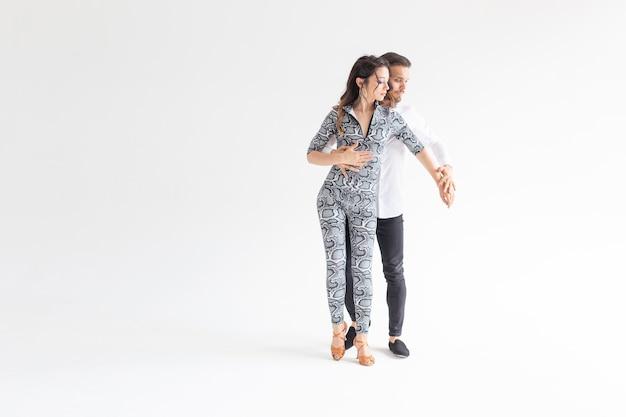 Conceito de dança social - adultos felizes e ativos dançando bachata juntos sobre um fundo branco com espaço de cópia