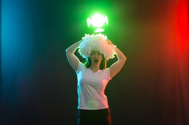 Conceito de dança, torcida e pessoas - jovem na escuridão sob uma luz colorida com pompons na cabeça.