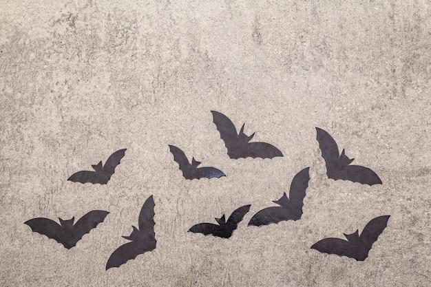 Conceito de decoração de halloween - morcegos pretos sobre fundo de concreto de pedra cinza