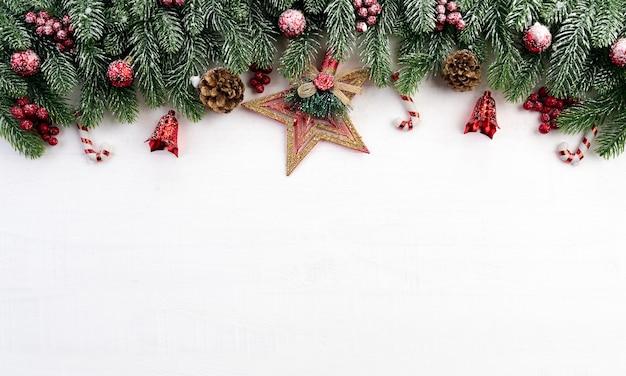 Conceito de decoração de ramos de natal com bagas, estrelas e pinhas em fundo branco de madeira.