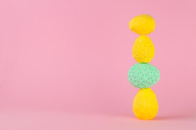 Conceito de decoração minimalista de páscoa. ovos de páscoa geométricos em cima uns dos outros em um fundo rosa com espaço em branco para texto.