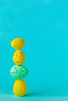 Conceito de decoração minimalista de páscoa. ovos de páscoa geométricos em cima uns dos outros na parede azul com espaço em branco para texto.