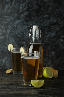 Conceito de deliciosa bebida com copos e garrafa de cerveja de gengibre na mesa de madeira
