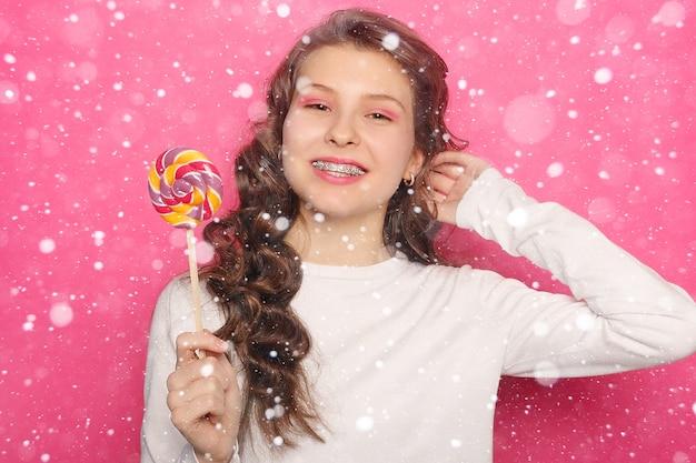 Conceito de dentes, emoções, saúde, pessoas, dentista e estilo de vida - mulher com aparelho dentário segurando pirulito. mulher com sorriso saudável e colchetes claros