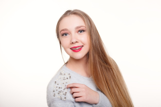 Conceito de dentes, emoções, saúde, pessoas, dentista e estilo de vida - sorriso bonito e saudável, a criança ao dentista. retrato de uma menina com aparelho ortodôntico.