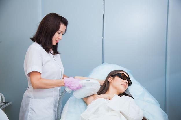 Conceito de depilação a laser, fotoepilação, corpo e cuidados com a pele. jovem mulher remove o cabelo das axilas na clínica de cosmetologia. close up, conceito de procedimento de higiene