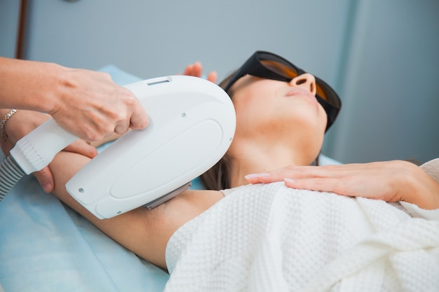 Conceito de depilação a laser, fotoepilação, corpo e cuidados com a pele. jovem mulher remove o cabelo das axilas na clínica de cosmetologia. close up, fêmea irreconhecível