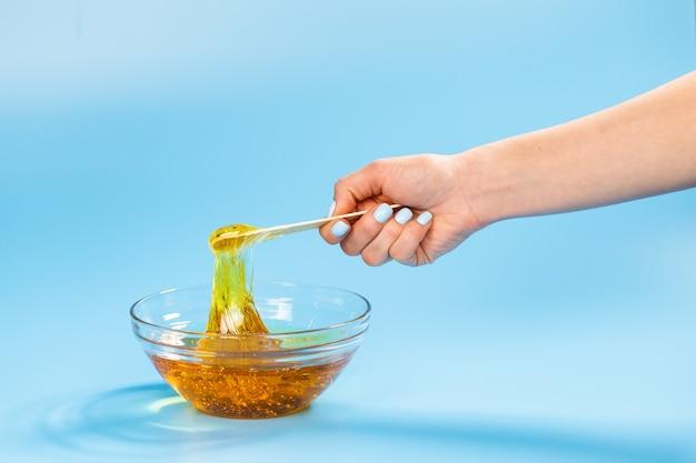 Conceito de depilação e beleza - pasta de açúcar ou cera de mel para depilação com espátula de madeira