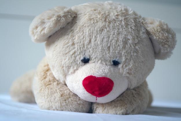 Conceito de depressão pesar de crianças, o ursinho de pelúcia dorme tristemente na cama,