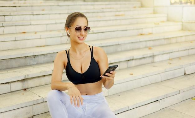 Conceito de descanso após o treino. jovem mulher esportiva em roupas esportivas usa smartphone e ouve música em fones de ouvido enquanto está sentada na escada em um dia ensolarado