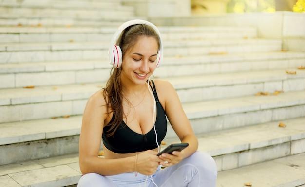 Conceito de descanso após o treino. jovem mulher feliz em trajes esportivos usa smartphone e ouve música em fones de ouvido enquanto está sentada na escada em um dia ensolarado