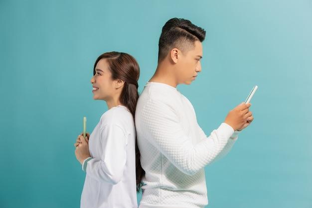 Conceito de desconfiança. lindo casal jovem e moderno com smartphones nas mãos, de costas um para o outro.